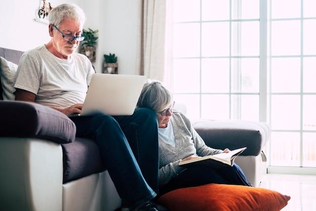 Coppia di anziani a casa - uomo con laptop e occhiali seduto sul divano - donna seduta sul grund che legge un libro - concetto di interni e amore