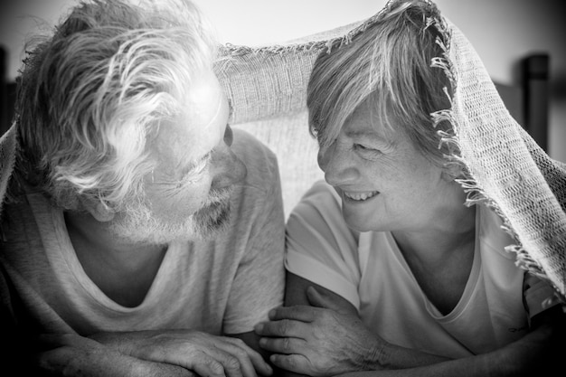 Coppia di anziani che guardano in mezzo e sorridono con amore e affetto sotto la coperta del letto - adulti in pensione e maturi sposati in camera da letto la mattina prima di alzarsi