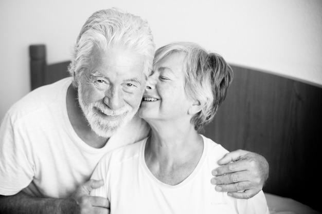 Coppia di anziani che guardano e sorridono con amore e affetto mentre lei lo bacia - adulti in pensione e maturi sposati in camera da letto la mattina prima di alzarsi