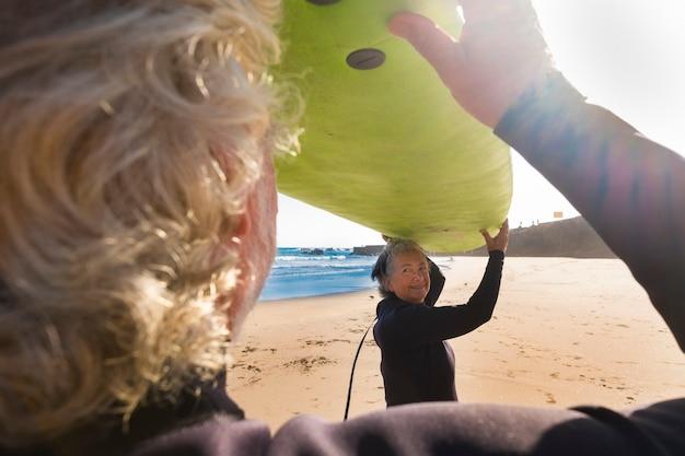 Coppia di anziani pronti per andare a fare surf in spiaggia tenendo insieme un grande tavolo da surf verde - provando la loro prima volta in una lezione di surf durante le loro vacanze