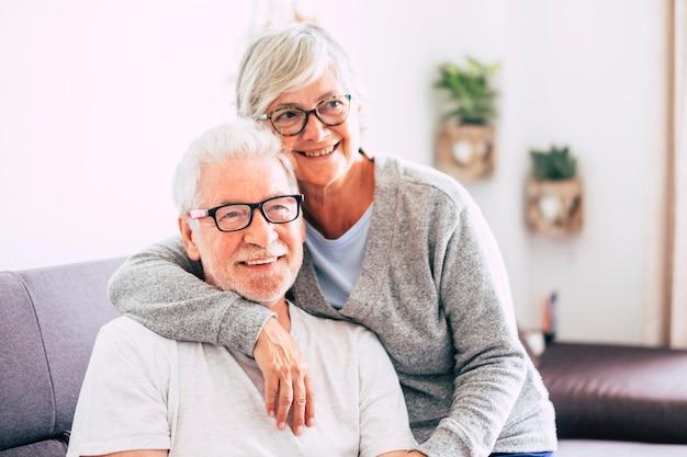 Coppia di anziani che sorridono e guardano la telecamera - donna che monopolizza l'uomo con amore sul divano - indoor