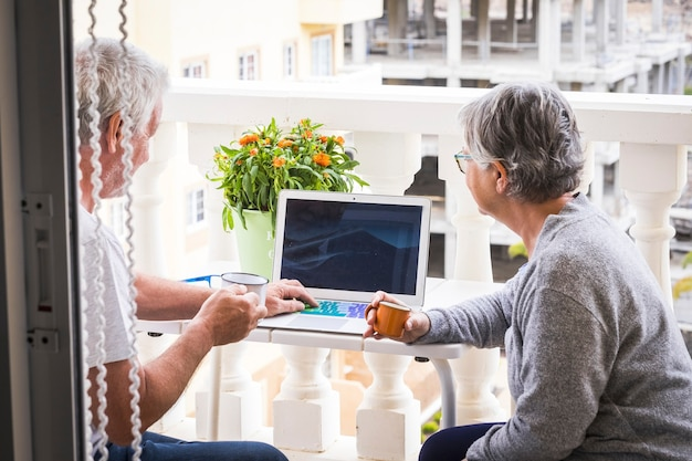 Coppia di anziani che sorridono e guardano il computer con caffè e laptop in terrazza - stile di vita all'aperto e all'aperto - sposati in pensione felici e godendosi questo momento