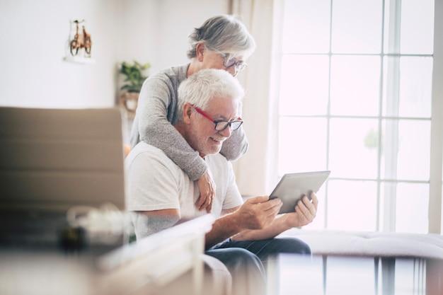 Coppia di anziani che sorridono e guardano lo stesso tablet abbracciati sul divano - concetto interno, a casa - caucasici uomo e donna maturi e pensionati che usano la tecnologia