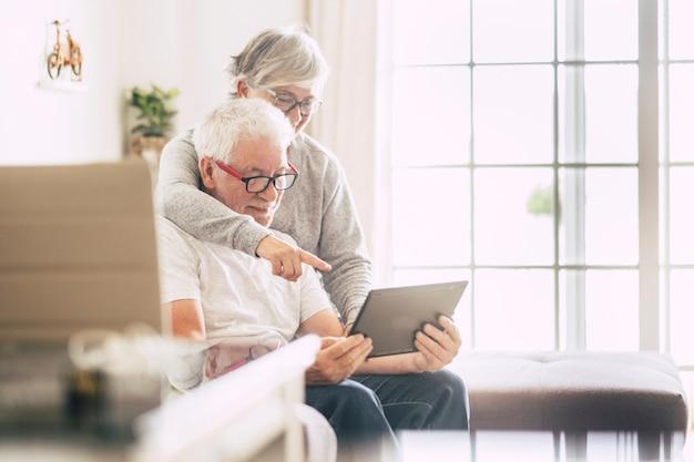 Coppia di anziani che sorridono e guardano il tablet - donna che monopolizza l'uomo con amore sul divano - indoor - mostrando