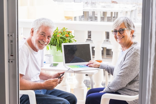 Coppia di anziani sulla terrazza divertirsi e divertirsi - uomo con laptop e caffè che mostra qualcosa a sua moglie - donna con caffè e occhiali guardando e sorridendo alla telecamera - all'aperto