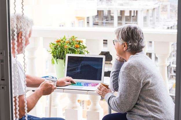 Coppia di anziani sulla terrazza divertirsi e divertirsi - uomo con laptop che mostra qualcosa a sua moglie - donna con caffè e occhiali guardando e sorridendo all'uomo - all'aperto