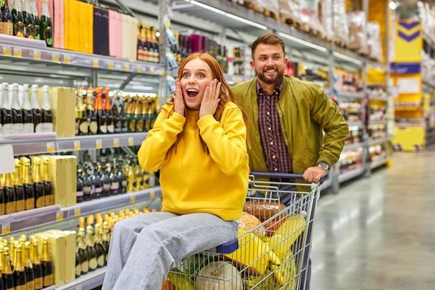 Coppia fare shopping insieme al supermercato, l'uomo porta la sua ragazza rossa sul carrello, si divertono, si godono il tempo, la donna è sorpresa felice
