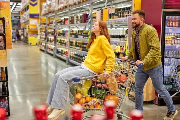 Coppia fare shopping insieme al supermercato, l'uomo porta la sua ragazza rossa sul carrello, si divertono, si godono il tempo