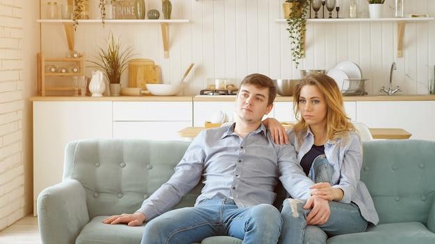 La coppia si siede sull'accogliente divano blu a guardare la tv in cucina moderna, la luce del sole