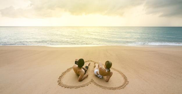Coppia seduta sulla spiaggia nel disegno a forma di cuore sulla sabbia. durante il tramonto in estate.