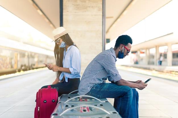 Coppia seduta su una panchina tra due ferrovia