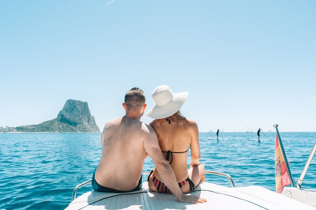 Coppia seduta sul ponte della barca godendosi la vista sul mar mediterraneo