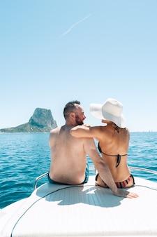 Coppia seduta sul ponte della barca godendosi la vista sul mar mediterraneo Foto Premium