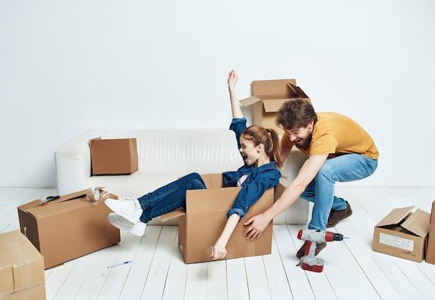 Coppia seduta sulle scatole del divano con le cose che rinnovano l'inaugurazione della casa
