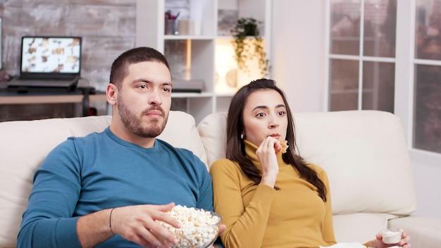 Coppia seduta sul divano a mangiare pollo fritto e popcorn mentre si guarda la tv. coppia spaventata dopo un momento spaventoso nel film.