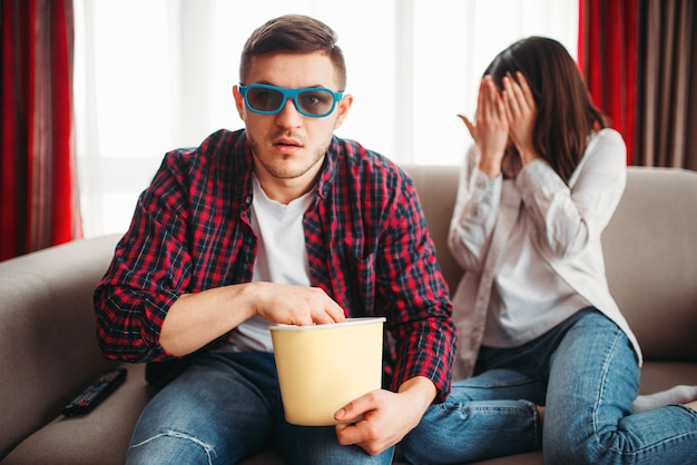 Coppia seduta sul divano, uomo in occhiali 3d con popcorn in mano guarda film, donna spaventata chiude il viso con le mani