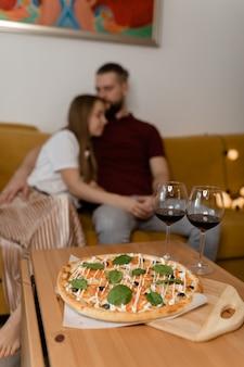 Coppia seduta in un abbraccio sul divano. c'è del vino sulla tavola. data di san valentino