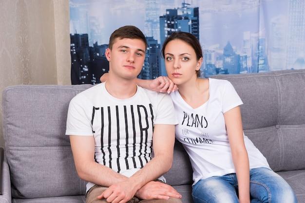 Coppia seduta abbracciata su un divano insieme a casa in un'atmosfera rilassata
