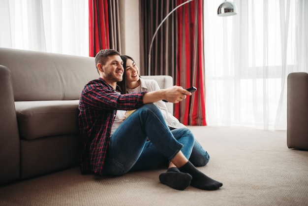 Coppia seduta sul pavimento abbraccia e guarda film