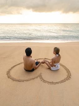 Coppia seduta nel cuore disegno sulla spiaggia di sabbia rilassante per prendere il sole.