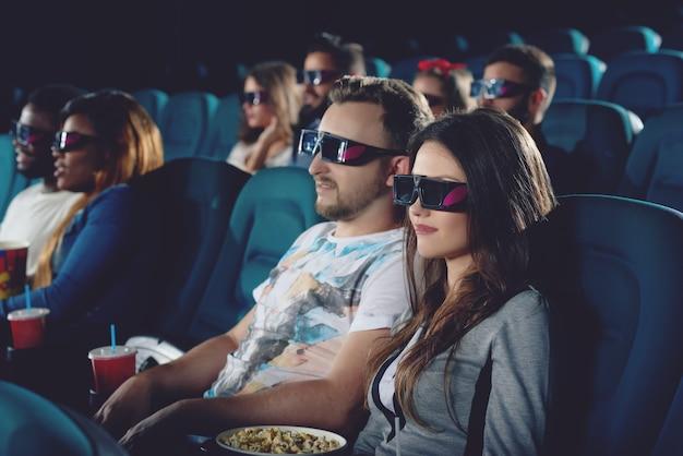 Coppia seduta in una moderna e confortevole sala cinema e guardare film. bel ragazzo e ragazza bruna che indossano occhiali 3d, guardando seriamente il proiettore.