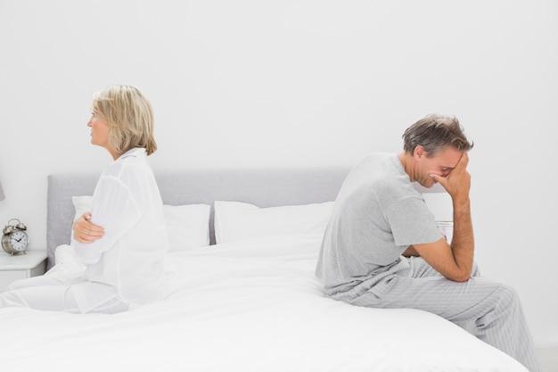 Coppia seduta sui lati opposti del letto