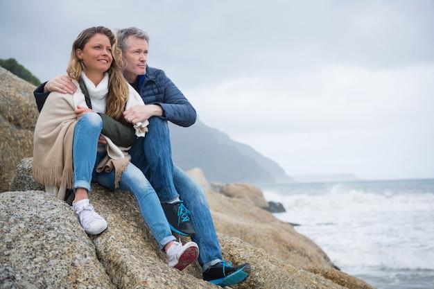 Coppia seduta sulle rocce e godersi la vista