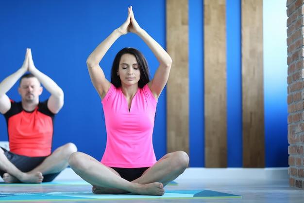 Coppia la seduta sulle coperte in una posa di yoga