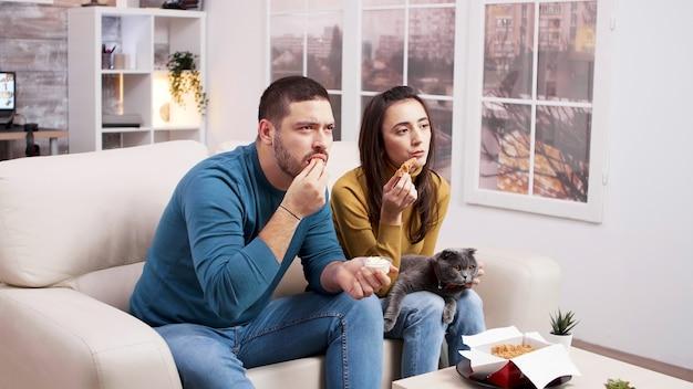 Coppia seduta sul divano a mangiare pollo fritto mentre guarda la tv con il gatto in grembo alla ragazza. coppia mangiare cibo spazzatura.