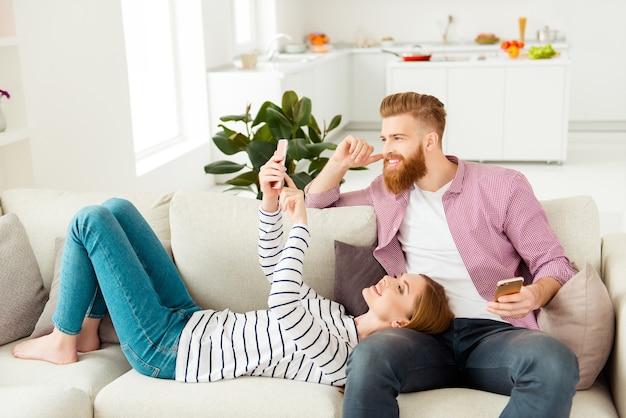 Coppia seduta sul divano di casa e godersi il loro tempo