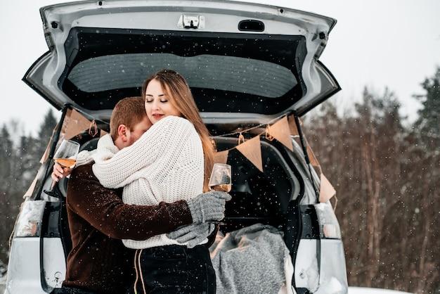 Una coppia seduta con le tazze sul retro di un'auto e fare un picnic in una foresta di neve