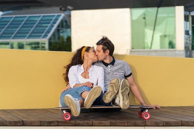 Coppia di pattinatori che si baciano si siedono sul longboard insieme all'aperto nello spazio urbano romanticismo e amore giovanile