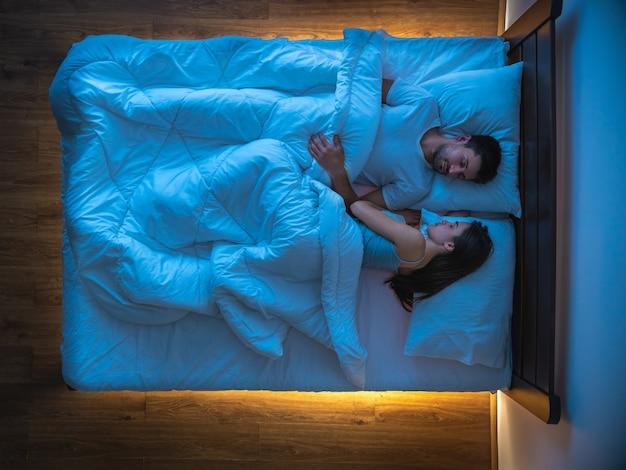 La coppia che dorme sul letto. vista dall'alto, serale notturno