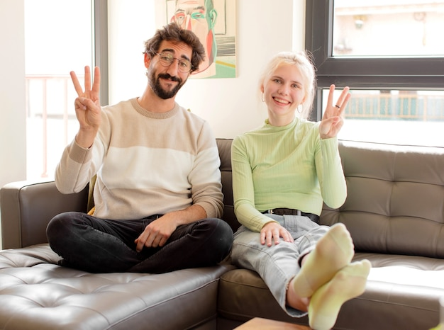 Coppia sorridente e guardando amichevole, mostrando il numero tre o terzo con la mano in avanti, il conto alla rovescia