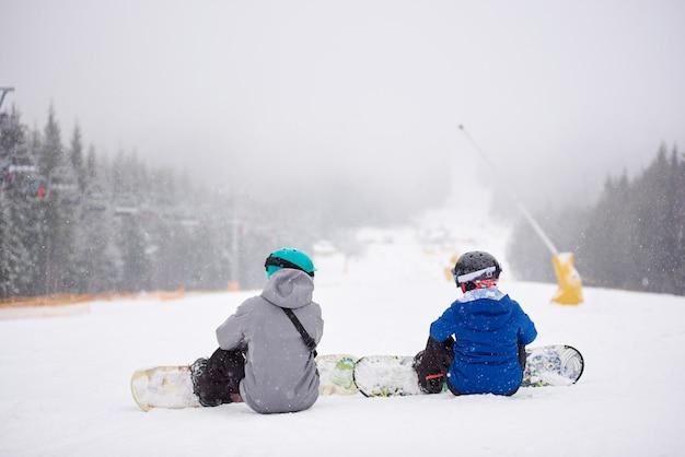 Snowboarder delle coppie che si siedono sulla neve sulla pista boscosa della pista da sci alla stazione sciistica in nevicata con le loro tavole su vista posteriore