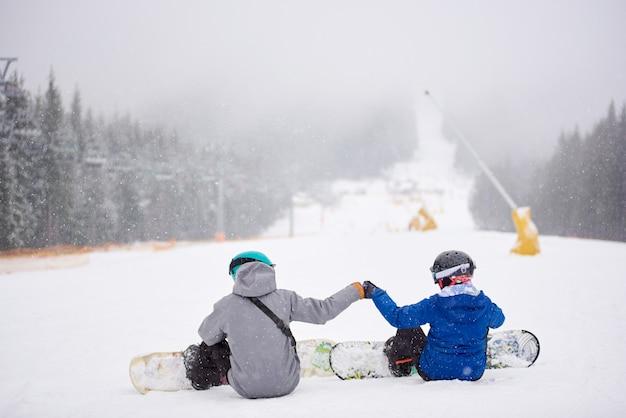 Snowboarder delle coppie che si siedono sulla neve sulla pista boscosa della pista da sci alla stazione sciistica