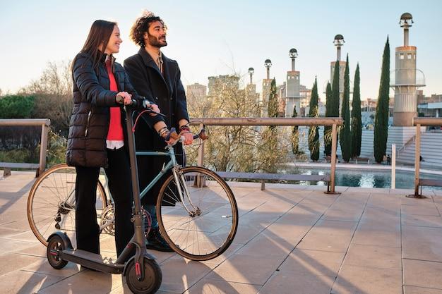 Coppie che trascorrono del buon tempo insieme mentre si cammina all'aperto con uno scooter elettrico e una bicicletta. concetto urbano.