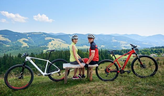 Sportivo di coppia vicino a biciclette in montagna