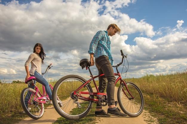 La coppia sta con una bicicletta all'aperto