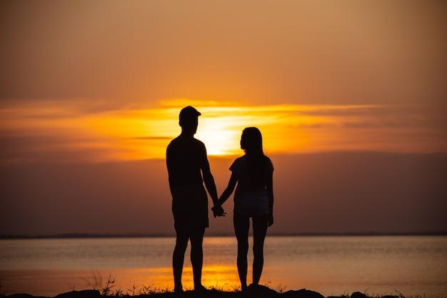La coppia in piedi vicino a un'acqua sullo sfondo dell'alba
