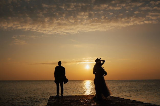 Coppia in piedi in riva al mare al tramonto bellissimo