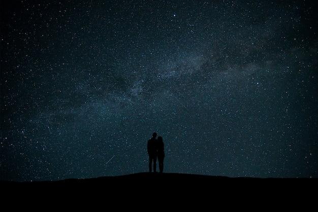 La coppia in piedi nel cielo con sfondo di stelle