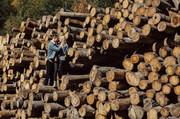 Coppia in piedi sulla catasta di legna da ardere