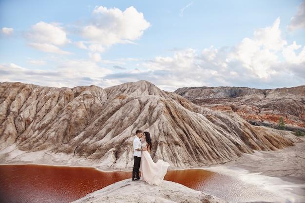 La coppia si trova sul precipizio della montagna e del lago rosso e si abbraccia. gli sposi innamorati, la donna in abito lungo tra le braccia degli uomini