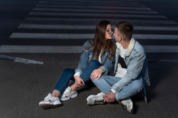 Coppia di studenti innamorati sono seduti per strada a tarda sera. una ragazza e un ragazzo ad un appuntamento. primo bacio.