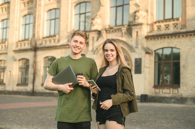 Coppia di studenti in piedi vicino all'università con il caffè
