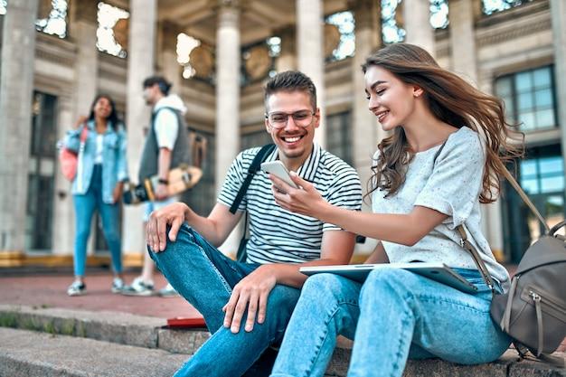 Una coppia di studenti con zaini e laptop si siedono sui gradini vicino al campus.