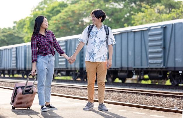 Coppia di turisti alla moda con zaini e che vanno in treno alla stazione della metropolitana all'aperto, concetto di stile vintage della stazione ferroviaria di viaggio di coppia asiatica, in thailandia