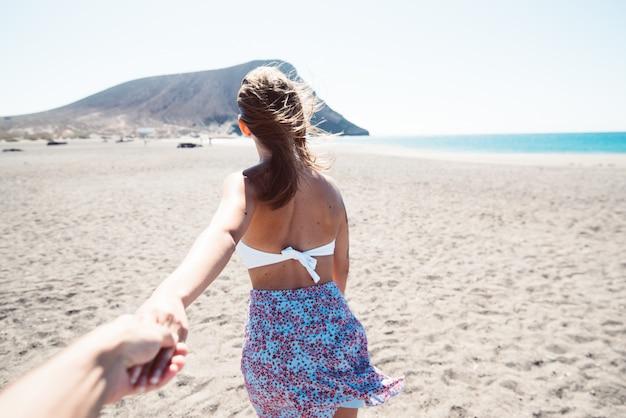 Coppia viaggio vacanze estive. donna che cammina tenendo la mano del marito che la segue, vista da dietro