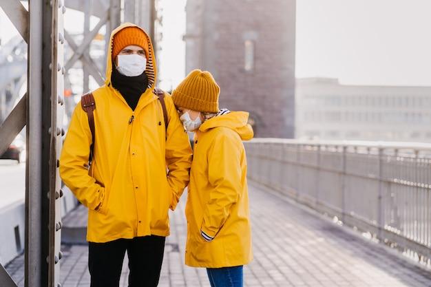 Sul ponte sono in piedi una coppia in maschere chirurgiche vestite con giacche gialle, confuse a causa del coronavirus. la ragazza è sepolta con preoccupazione nella spalla del suo ragazzo. concetto di covid-19.